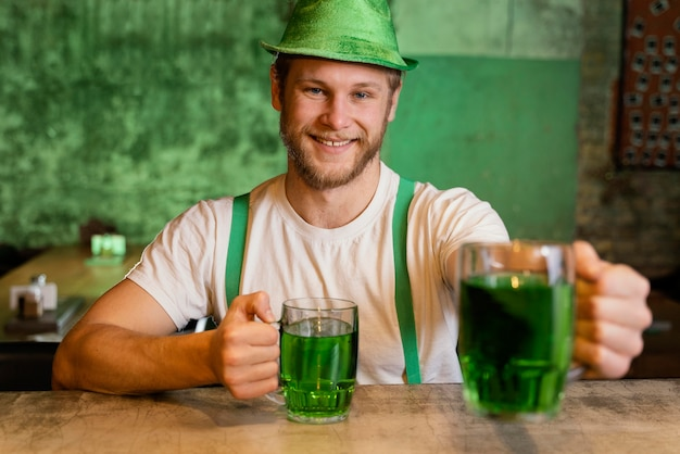 Uomo bello che celebra st. patrick's day con drink al bar