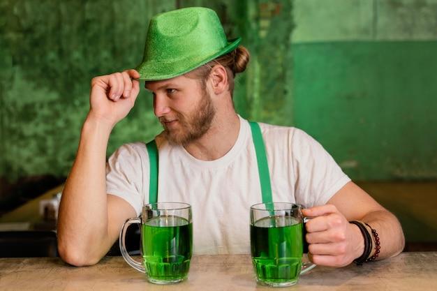Красивый мужчина празднует ул. день патрика с напитками
