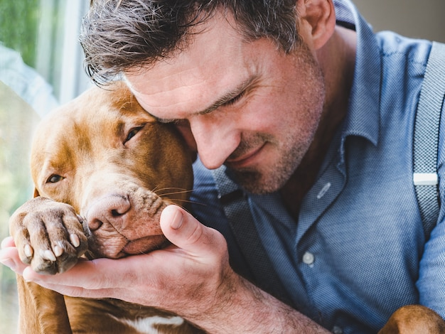 Handsome man and a charming puppy. close-up