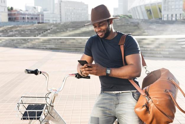 Красивый мужчина проверяет свой телефон на велосипеде