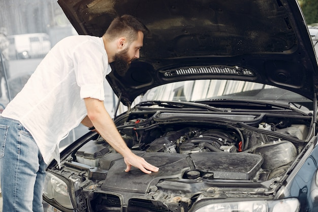 Красивый мужчина проверяет двигатель в своей машине