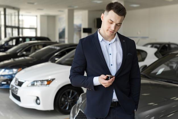 Красивый мужчина выбирает машину в выставочном зале