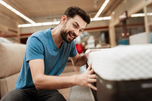 Handsome man choosing mattress in furniture store