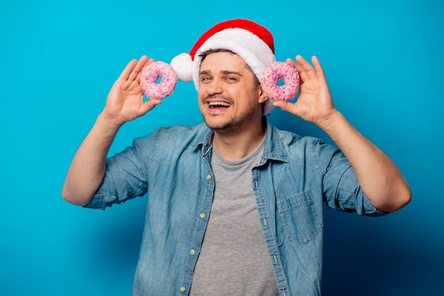 Handsome man in christmas hat with donuts
