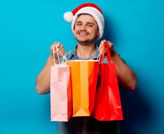 Handsome man in christmas hat with shopping bags