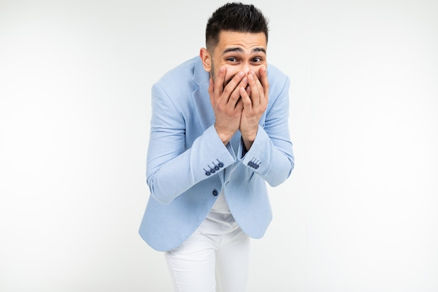 Handsome man in classic style laughs covering his mouth with his hand on a white background isolated