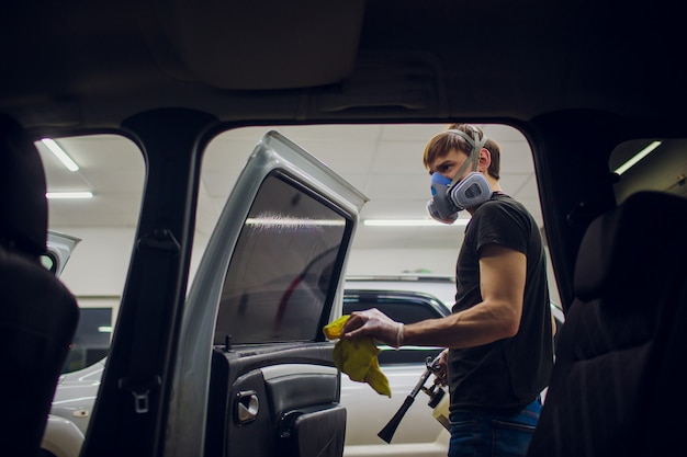 Handsome man cleaning car with hot steam