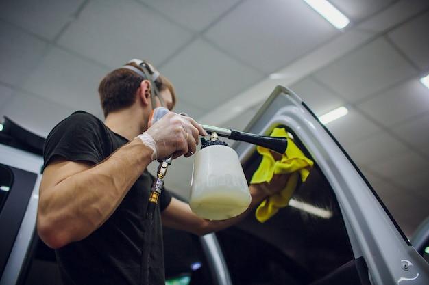 Красивый мужчина чистит машину горячим паром
