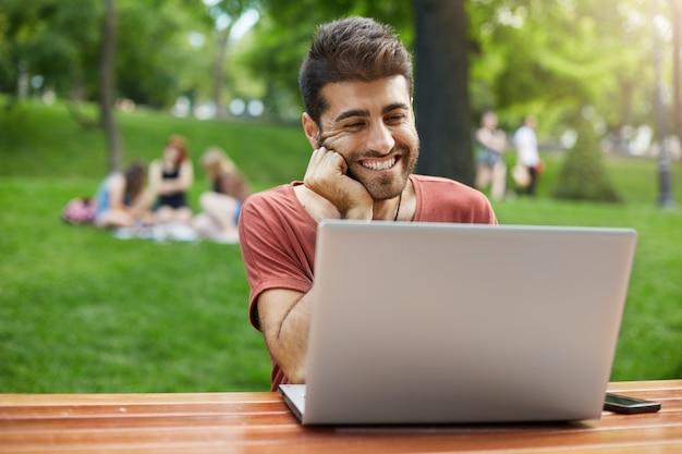 Красивый мужчина соединяет wi-fi в парке и друга по видеосвязи с ноутбуком