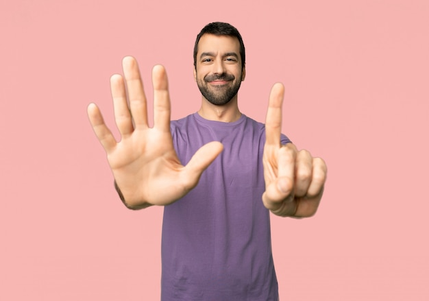 Handsome man counting six with fingers on isolated pink background