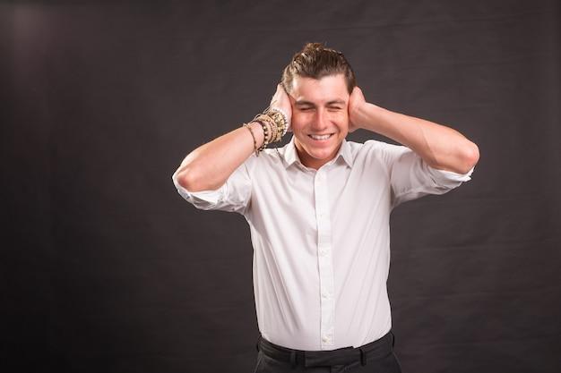 両手で耳を覆い、茶色の表面でカメラを見ているハンサムな男