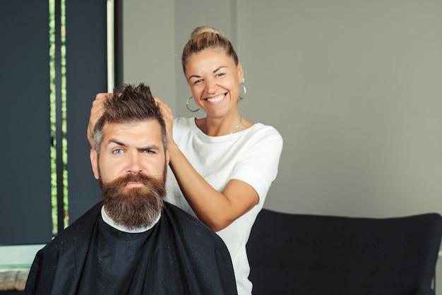 ハンサムな男はひげと口ひげをカットして剃ります。ひげのスタイリングとカット。あごひげを生やした、長いあごひげ、残忍な、口ひげを生やした白人のヒップスター。