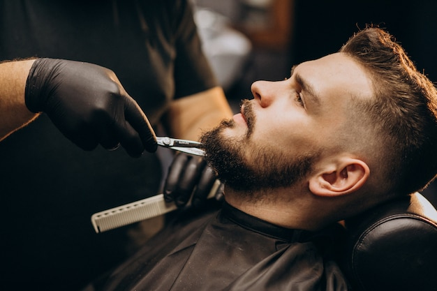 Красавец стричь бороду в парикмахерской