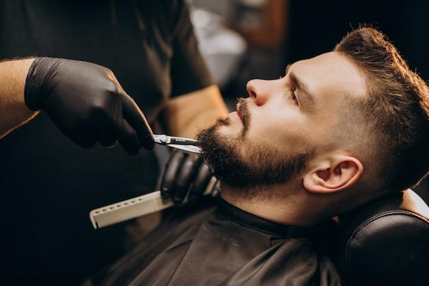 Barba di taglio uomo bello in un salone del negozio di barbiere
