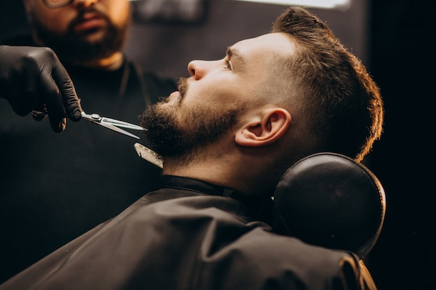 Handsome man cutting beard at a barber shop salon