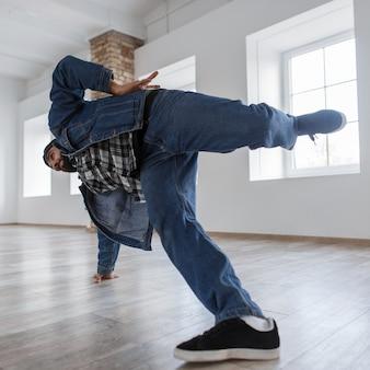 Красивый мужчина танцор в джинсовой куртке и джинсах танцует брейк-данс в танцевальной студии
