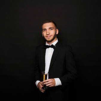 Handsome man in dinner jacket with glass of drink