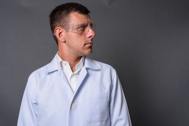 Handsome man doctor wearing protective glasses against gray back