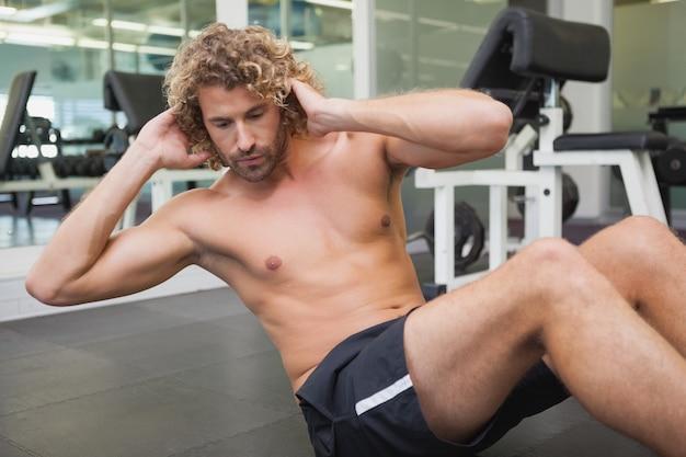 Handsome man doing abdominal crunches in gym