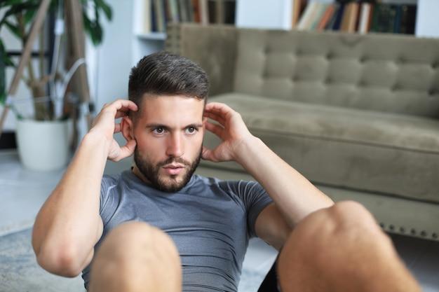 検疫中に自宅で腹筋運動をしているハンサムな男。健康的な生活の概念