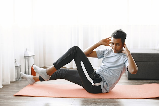 Handsome man doing abs exercises at home. concept of healthy life.