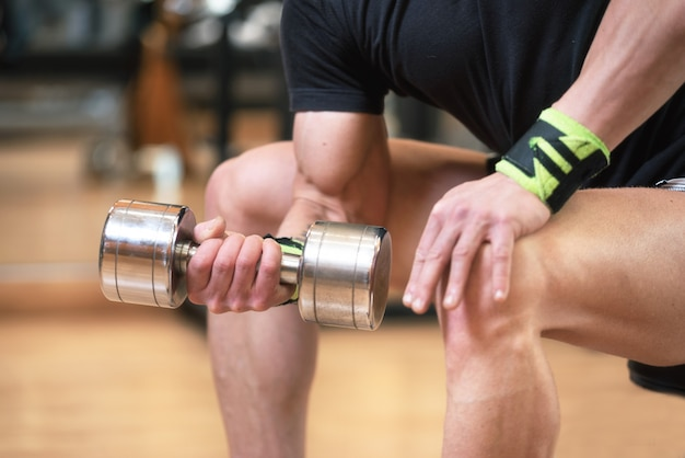 Handsome man doing biceps lifting with dumbbell on bench in a gym.