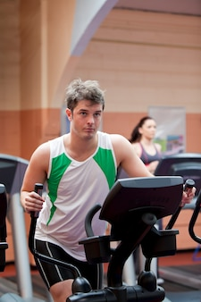Handsome man doing exercises using cross trainer in a fitness centre