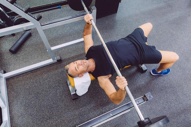 フィットネスセンターでベンチプレストレーニングでバーベルでエクササイズをしているハンサムな男