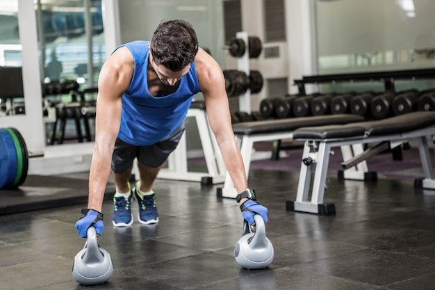Handsome man doing push ups with kettlebells in the gym