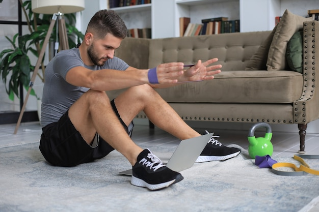 検疫中に自宅でスポーツ運動をしているハンサムな男。健康的な生活の概念