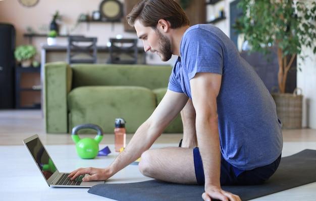 Красивый мужчина занимается спортом дома во время карантина. концепция здорового образа жизни.