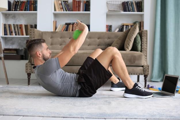 自宅でケトルベルでスポーツ運動をしているハンサムな男。健康的な生活の概念。