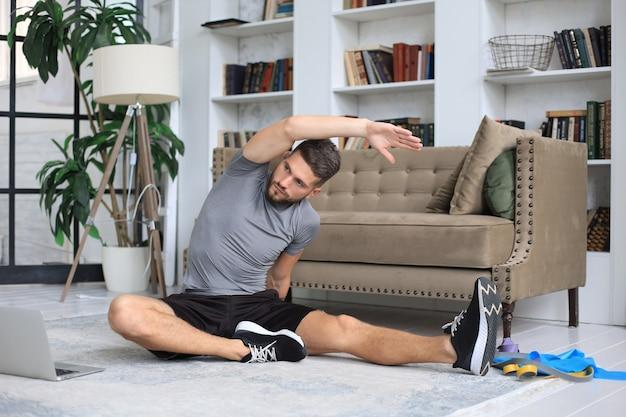 検疫中に自宅でストレッチ運動をしているハンサムな男。健康的な生活の概念