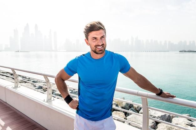 Красивый мужчина делает работу и различные упражнения на открытом воздухе
