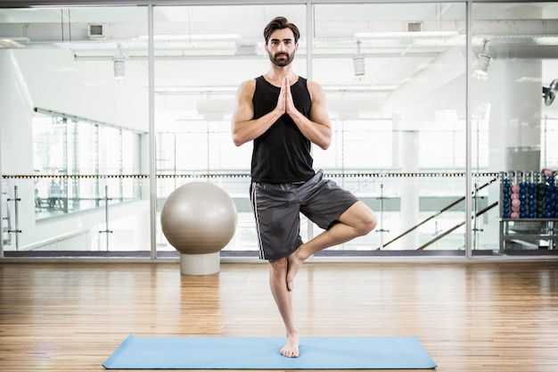 Handsome man doing yoga on mat in the studio