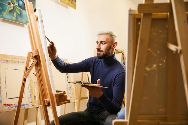 Красивый мужчина рисует картину маслом и улыбками