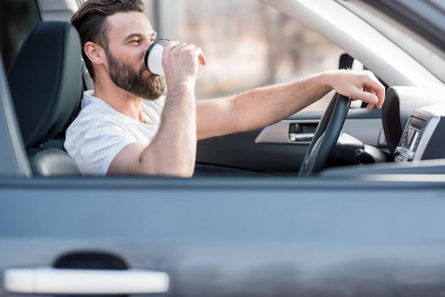 行くためにコーヒーで車を運転する白いtシャツを着たハンサムな男
