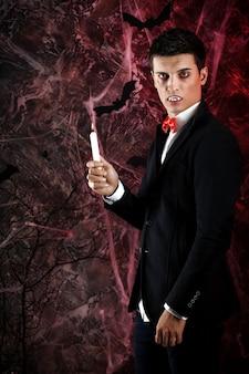 ハロウィーンのドラキュラの衣装を着たハンサムな男。ろうそくを持つ魅力的な吸血鬼