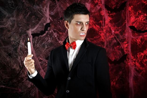 할로윈 드라큘라 의상을 입은 잘 생긴 남자. 초를 가진 매력적인 뱀파이어