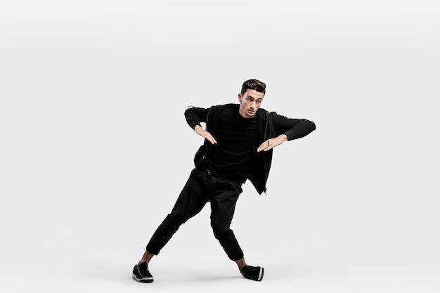 スタイリッシュな黒い服を着たハンサムな男がストリートダンスを踊っています