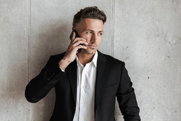 Handsome man dressed in suit talking on mobile phone