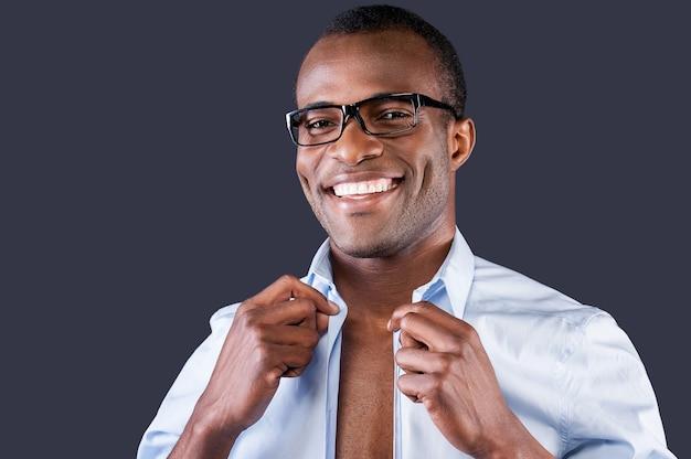 Красивый мужчина наряжается. красивый молодой темнокожий мужчина одевает рубашку и улыбается в камеру, стоя на сером фоне