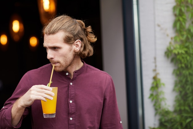 Handsome man drinking cocktail outdoors