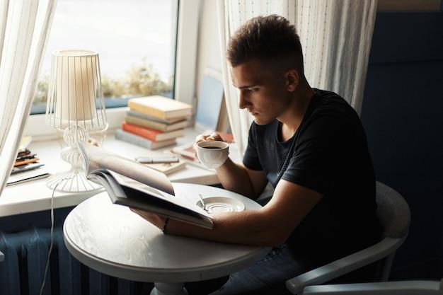 コーヒーを飲み、カフェテリアで雑誌を読むハンサムな男