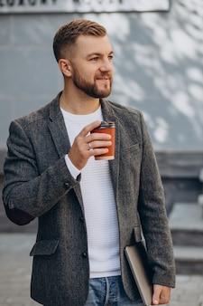 通りでコーヒーを飲むハンサムな男