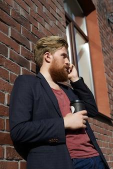 Uomo bello che beve caffè o tè e parla per telefono
