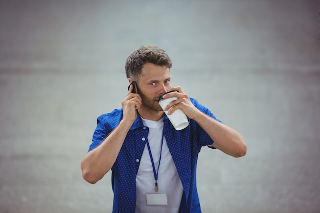Handsome man drinking coffee while talking on mobile phone