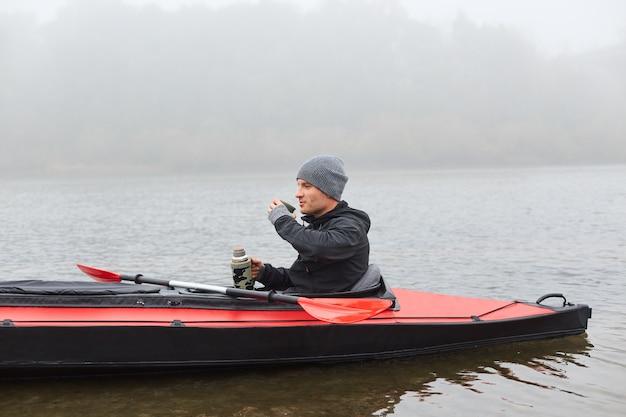 Красивый мужчина пьет чай из термоса и греется, сидя в каноэ посреди реки