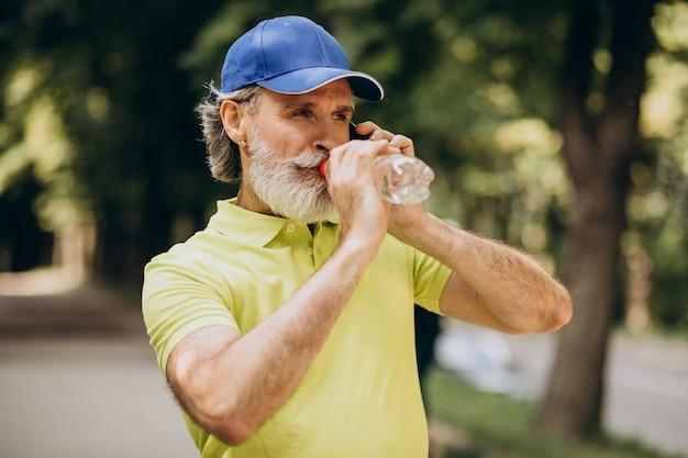 Красивый мужчина пьет воду в парке после пробежки
