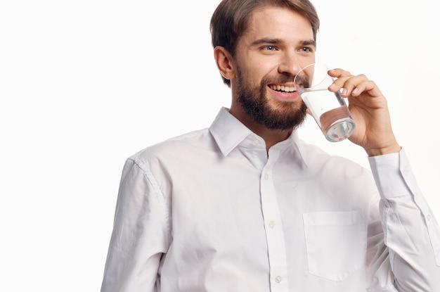 Красивый мужчина пьет воду светлом фоне